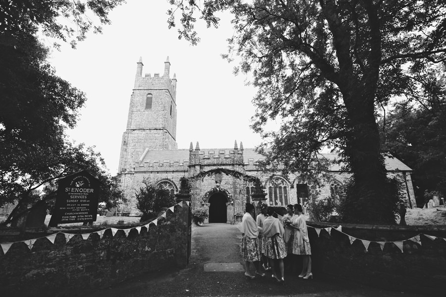 Bridesmaids standing outside St Enoder Church, Cornwall, England