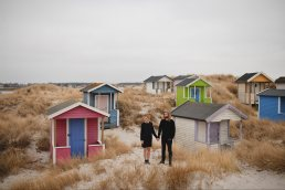 Wedding photographer Malmo - Couple posing in front of colorful wooden huts in Skanor Falsterbo, Sweeden