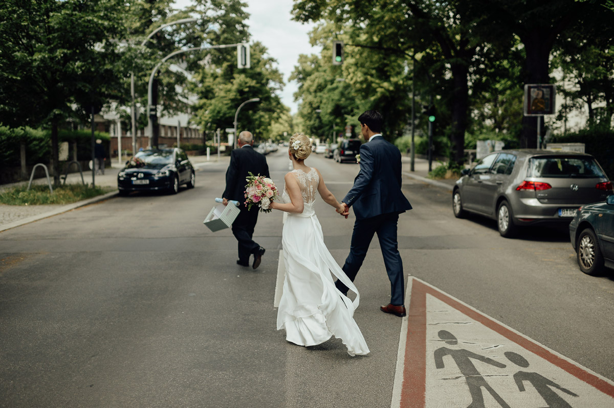 Wedding couple crossing road in Berlin