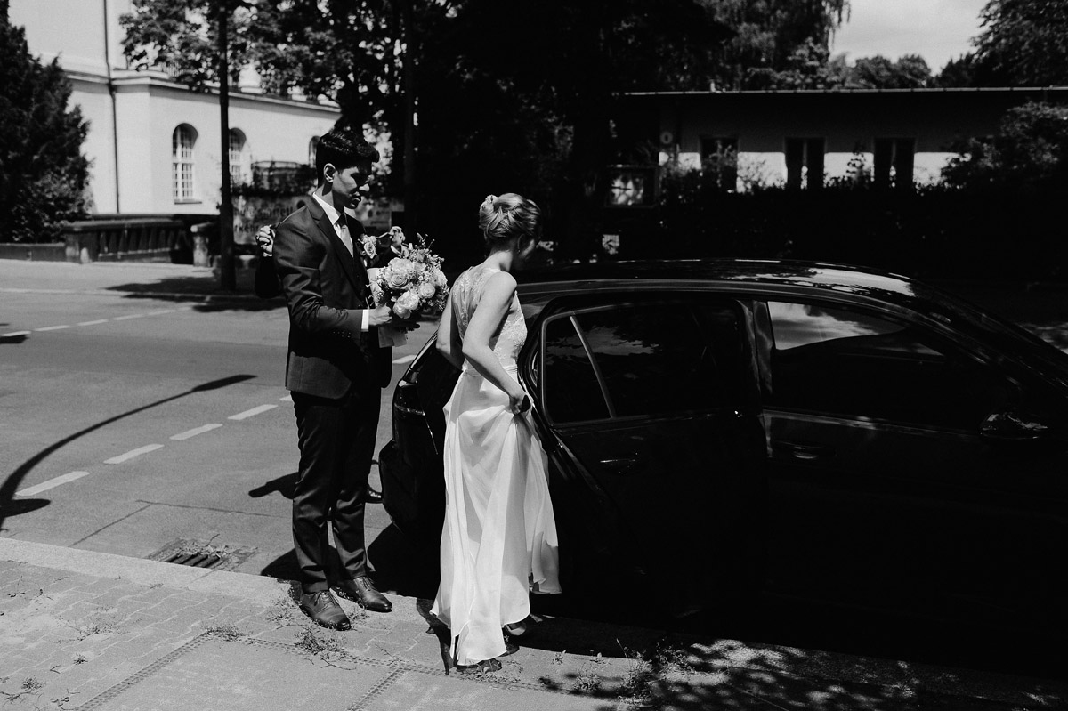 Wedding couple getting in car in Berlin