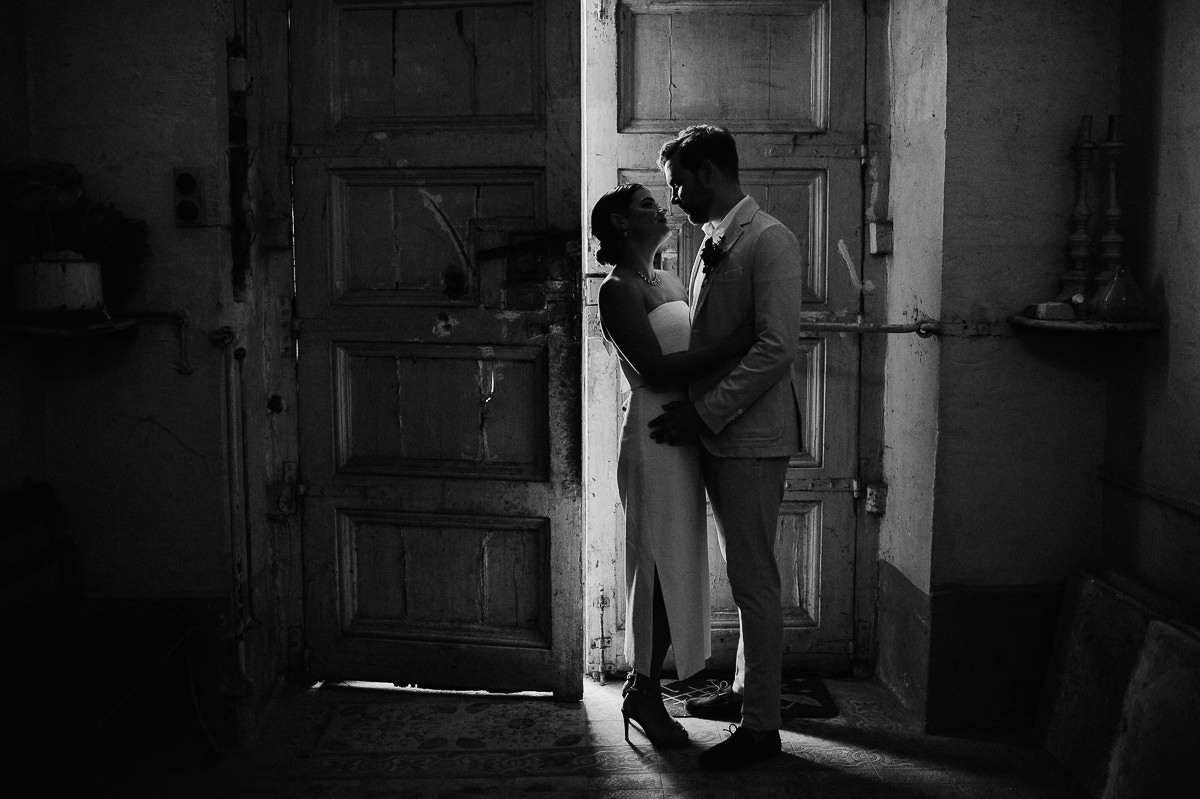 black and white wedding portrait of a couple standing in the light of an open door