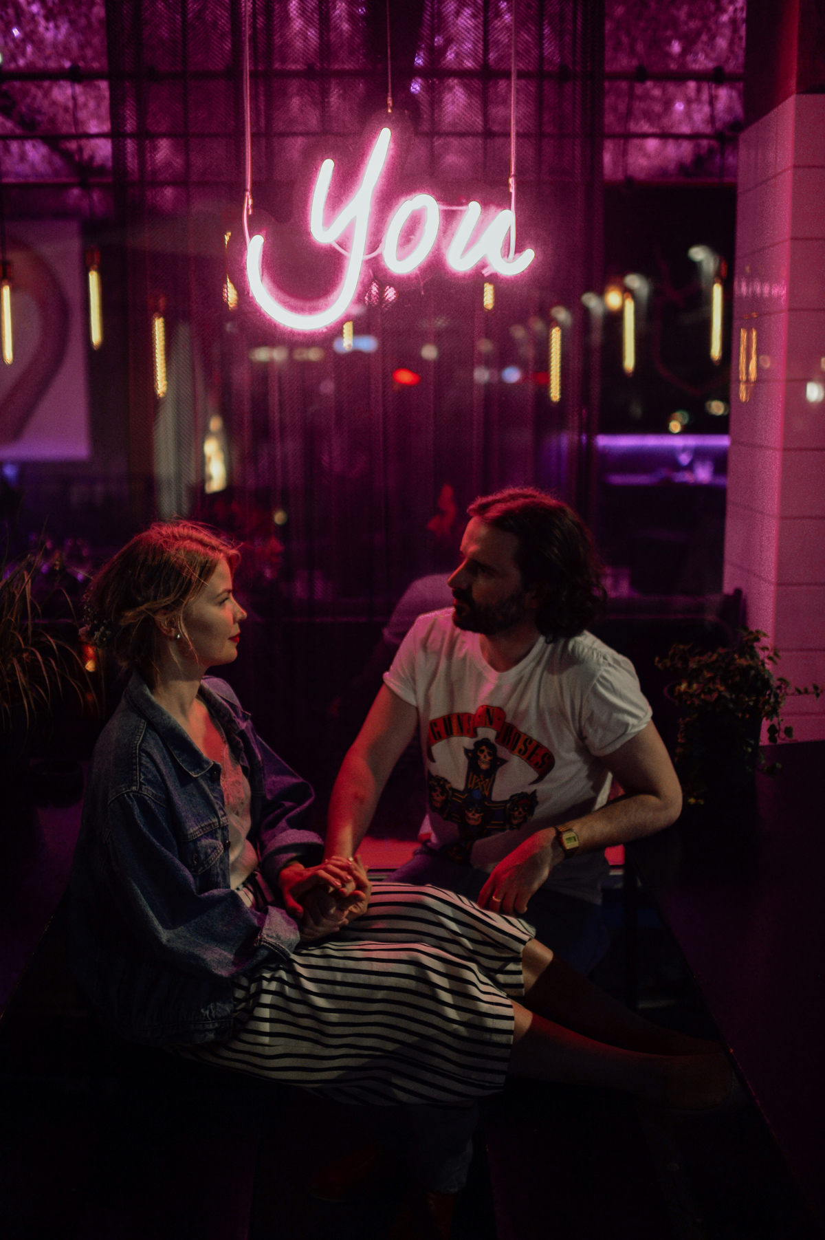 couple portraits at neon light in Copenhagen meat packing district
