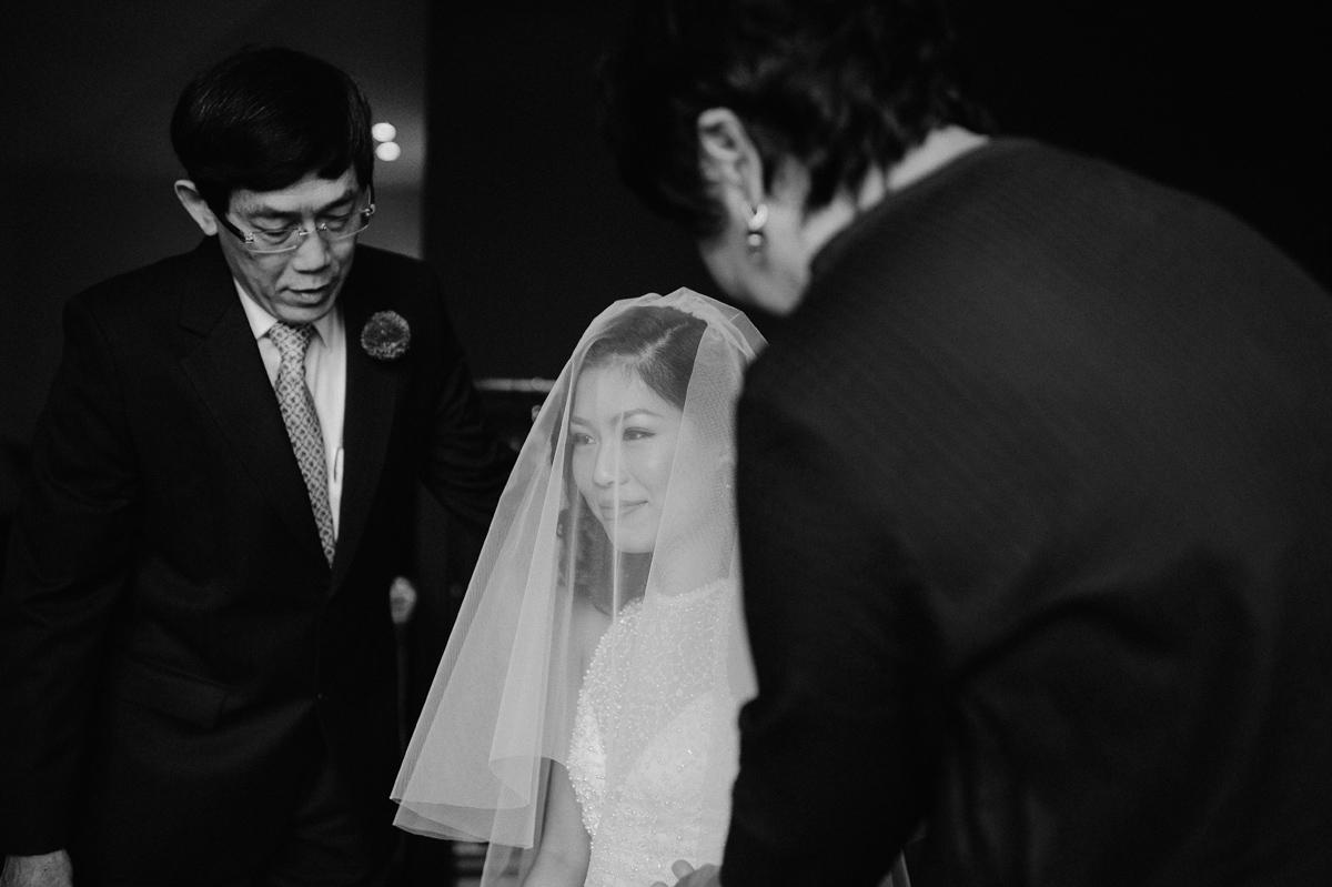 Parents putting the wedding veil on bride