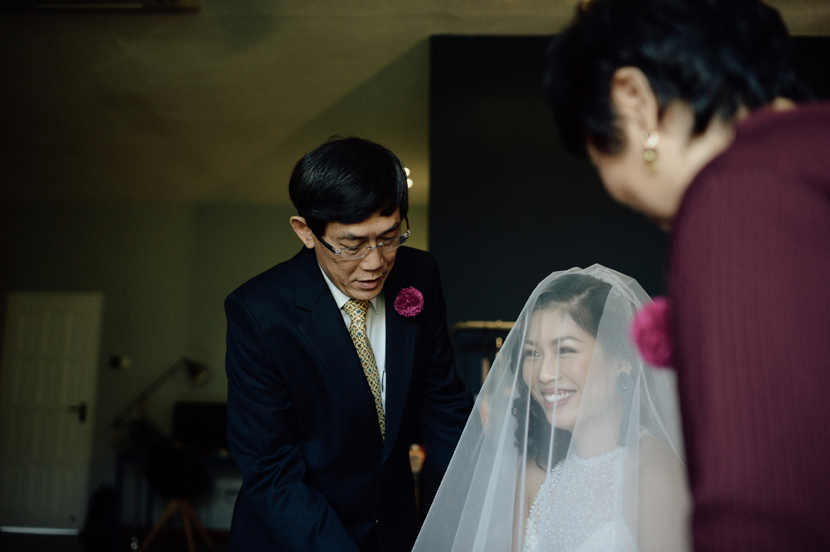Parents putting the wedding veil on bride