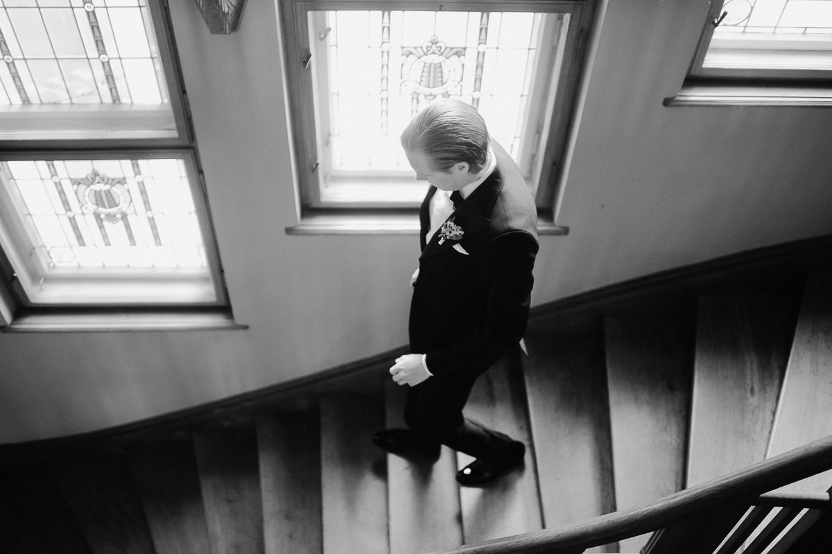 groom walking down staircase in Writer's Villa