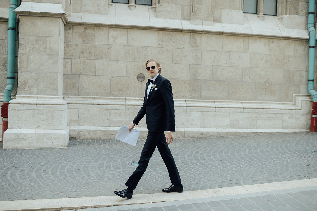 Groom walking in front of St Matthias church Budapest