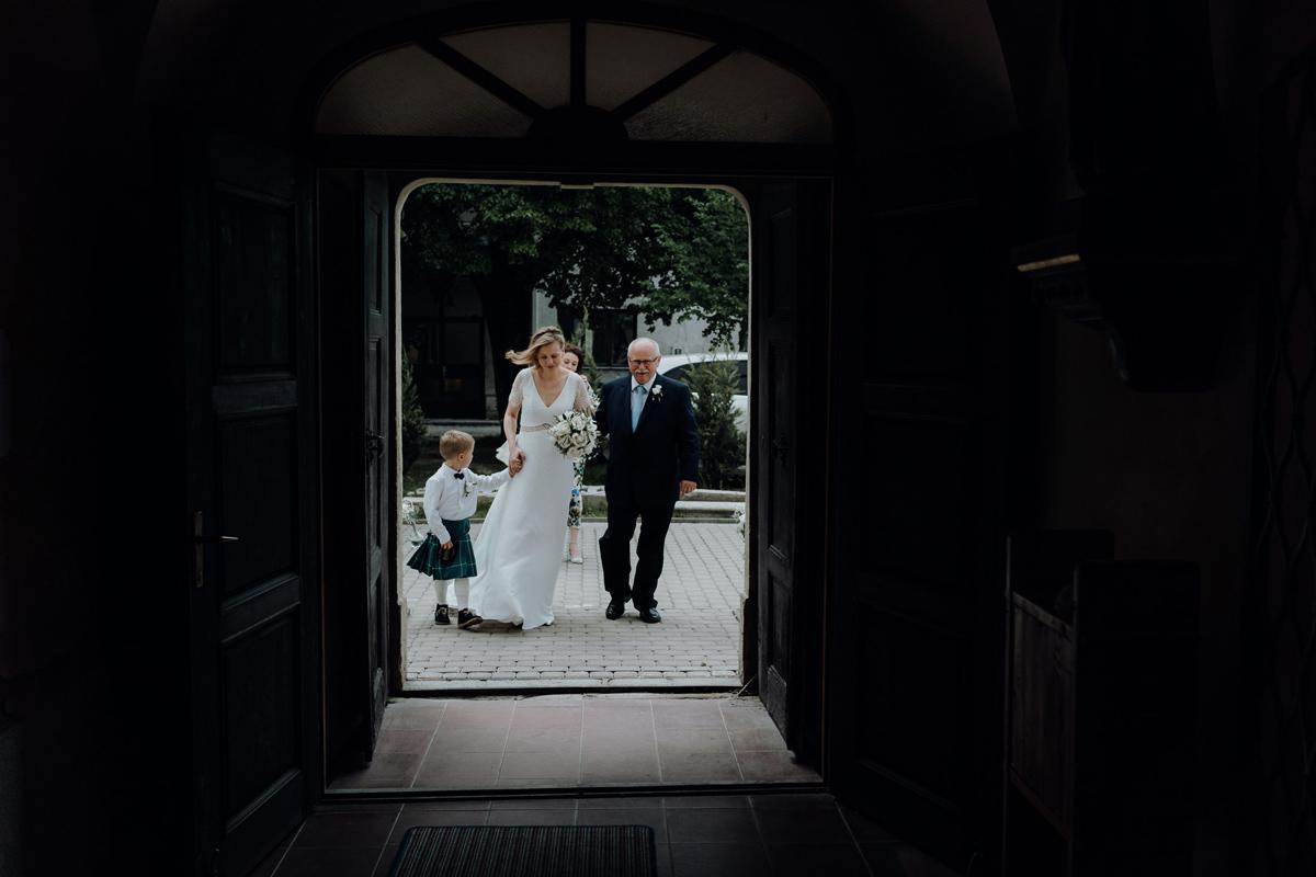 bride through the entrance of a church